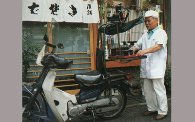 And now,Demae delivery service is practiced with motorbike equipped with the Demae device(1).  ((1)The Demae device is a special rack equipped on the back of a motorbike which swings and rocks on hinges to keep the food safe during transport.)